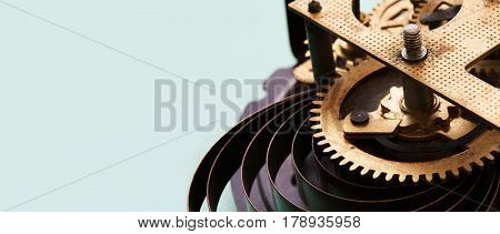Antique mechanic clock mechanism on blue background, bronze cogs wheels macro view. Shallow depth of field, selective focus. Copy space.