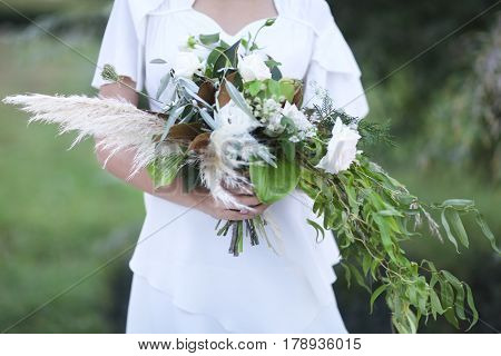 Young bride in white wedding dress holding beautiful bouquet over blurred outdoors background