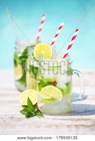 Glasses of lime lemonade near pool. Summer pool party