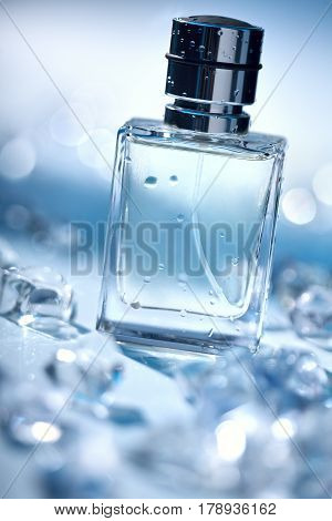 Perfume in glass transparent bottle with water droplets and pieces of ice around. Photo of bottle perfume on blurred blue background. Beauty concept