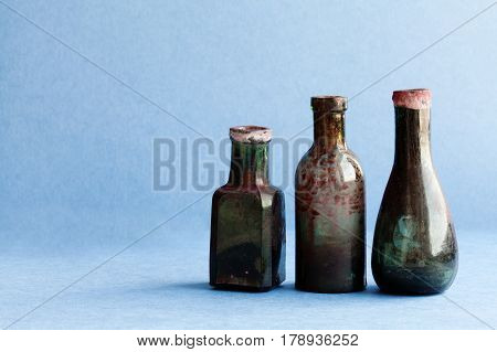 Vintage ink bottles on blue paper background. Aged dirty glass accessories. copy space, horizontal photo.