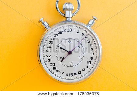 Retro style stopwatch chronometer on yellow paper textured background. Sport competition time management concept. Macro view, soft focus