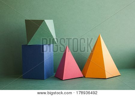 Abstract geometrical solid figures still life. Colorful three-dimensional pyramid prism rectangular cube arranged on green background. Yellow blue pink malachite colored objects textured paper surface.