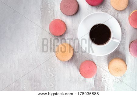 A photo of a cup of coffee with various pastel coloured macarons and a place for text