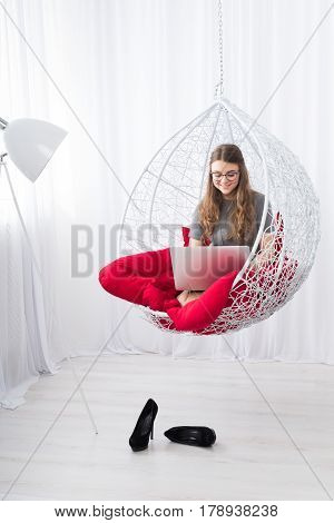 Beautiful woman in eyeglasses in fashionable armchair with laptop. Girl with pc in modern interior at red cushions. Stylish high key portrait of freelancer, work at home concept. Soft toning.