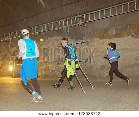 STOCKHOLM SWEDEN - MAR 25 2017: Man with crutches in reflex vest in a dark tunnel in the Stockholm Tunnel Run Citybanan 2017. March 25 2017 in Stockholm Sweden
