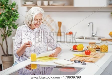 Happy old woman is reading document and smiling. She is sitting at table in kitchen