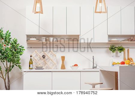 Modern domestic kitchen with white cupboards and vegetables on table