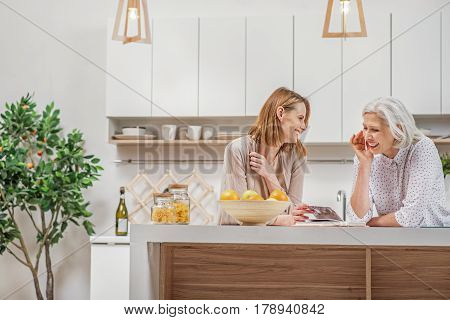 Happy senior mother and young daughter are watching album in kitchen. They are standing near table and laughing