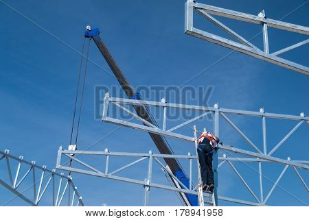 Crane lifting galvanized steel roof truss construction frames with deep blue sky in the background and construction worker assembling the elements