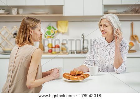Caring young daughter is visiting her senior mother at home. They are drinking tea with pastry and talking. Women are laughing