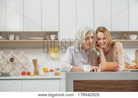Portrait of cheerful senior mother and daughter watching family album with joy. They are sitting at table and smiling. Copy space in left side