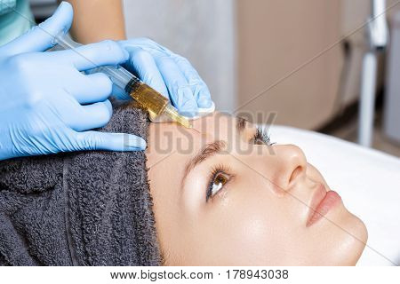 procedure Plasmolifting injection. plasma injection into the skin of the forehead of the patient poster
