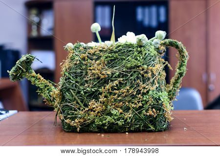 Woven from dried grass flowerpot in the shape of a watering can. Is in the office