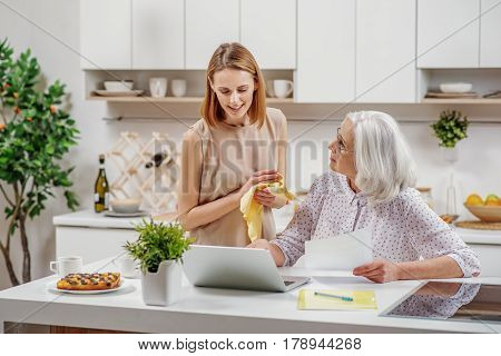 Puzzled mature woman is asking help in her daughter. She is sitting at table and pointing at laptop with misunderstanding. Young girl is standing and smiling