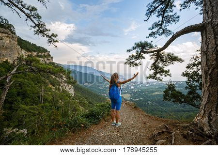 Cheering woman hiker open arms at mountain peak, Young girl spreading hands with joy and inspiration with backpack on facing Yalta city, healthy lifestyle and freedom concept