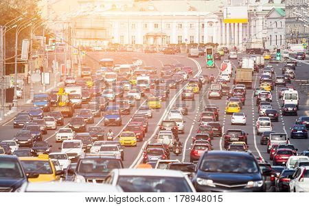 Lanes of a wide city street with lots of cars under the warm sunlight