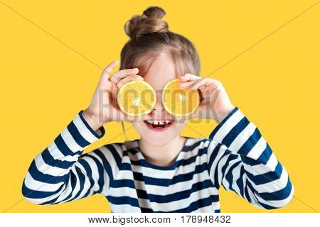 A girl with oranges on a background in the studio closes her eyes and laughs