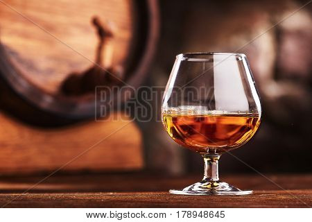 Glass of Cognac and old oak barrel defocussed
