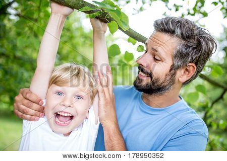 Laughing child climbs tree and father helps him