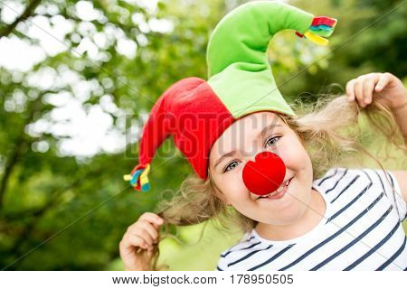 Cheerful girl as clown having fun at childrens birthday party