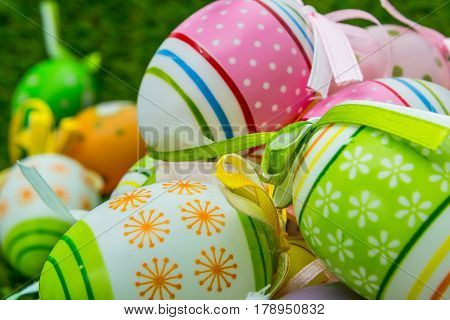 painted decorated Easter eggs and decorated Easter whip in spring grass