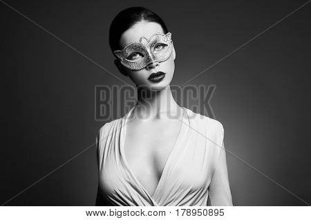 Portrait of young brunette woman against a dark background. Mysterious bright image of a woman with professional makeup. Sensuality and mystery of women. Hair care and skin. Face facial mask girls B&W