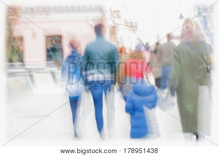 City in the early spring. Street, Families with children and other people walking along the sidewalk, blurred, background, concept shopping, walking, lifestyle. Space for text