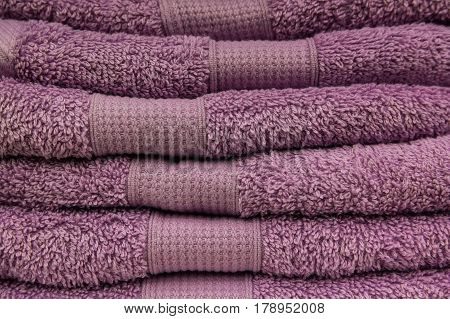 Home wardrobe with several purple towels lying on shelf