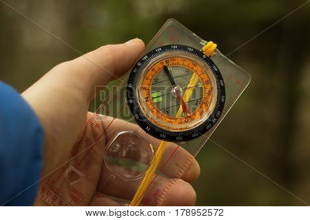 A compass in the hand of a tourist when you go camping through the forest you need to take with you this device if you get lost then he will indicate the way