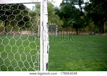 Soccer football net background over green grass and blurry stadium. Background of soccer football goal in stadium on match day