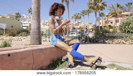 Female wearing rollerskates sitting on curb