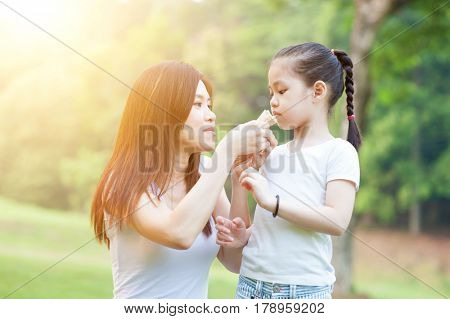 Lifestyle portrait of Asian mother and daughter eating sandwich in the park, Family outdoor fun, morning with sun flare.