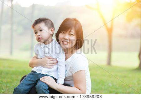 Mother hugging son in the park, Asian family outdoor lifestyle, morning with sun flare.