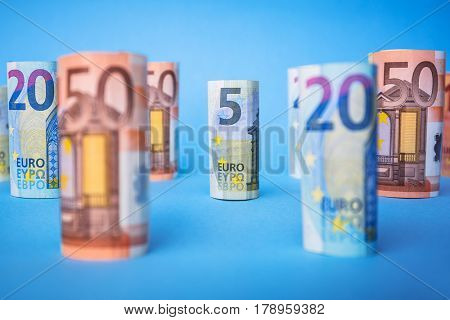 Rolled up euro banknotes on blue background. Selective focus