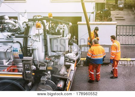 PARIS FRANCE - DEB 10 2017: Team working hard on the street using sewerage truck and large pipe - clogged street rain water drain repairing and maintenance