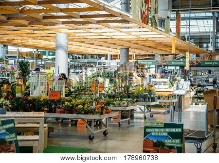 BUCHAREST ROMANIA - APR 1 2016: Two seniors men buying flowers for garden inside Hornbach the German DIY-store chain offering home improvement and do-it-yourself goods - customers buying goods selecting the best tools