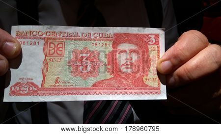 Unknown man holds Ernesto Che Guevara on a Cuban 3 pesos