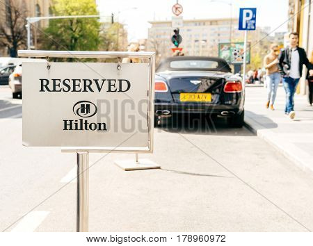BUCHAREST ROMANIA - APR 1 2016: Resrved parking sign in front of the Hilton five star luxury hotel with silhouette of Bentley luxury convertible care parked