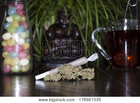 closeup of rolled marijuana weed joint and buds on wooden background with Buddha statuette colorful jellybeans and cup of rooibos tea