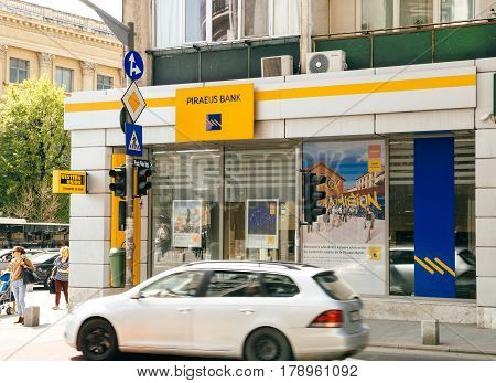 BUCHAREST ROMANIA - APR 1 2016: Piraeus Bank agency facade with customers walking in front and cars on the street. Piraeus Bank is a Greek multinational financial services company with its headquarters in Athens Greece.