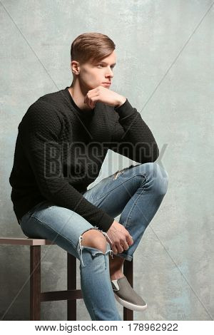 Handsome young man sitting near textured wall