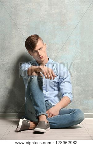 Handsome young man sitting on floor near textured wall