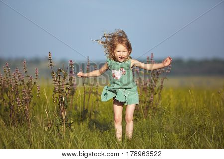 happy smiling girl in the field at sunny summer morning. girl in green dress Collects a bouquet of wildflowers and Jumping over the field cheerfully. The family travels, the children happily ran around the field