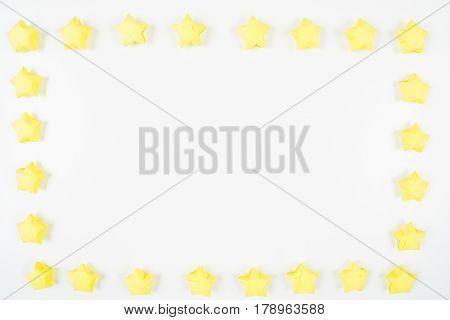 Yellow handmade paper stars frame on white background