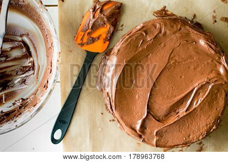 Chocolate cake on kitchen counter with a bowl and spatula. Frosted cake and empty bowl on messy counter.
