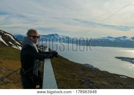 A beautiful girl looking at mountains inside artic circle