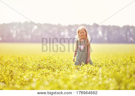 girl in the field at sunny summer morning. girl in green dress Runs into the field. The family travels, the children happily ran around the field