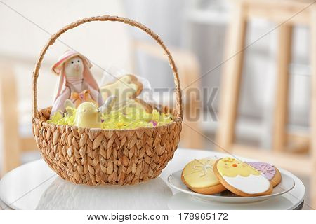 Easter basket with decorations and plate with delicious cookies on blurred background