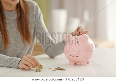 Beautiful young woman putting coins into piggy bank at home, closeup